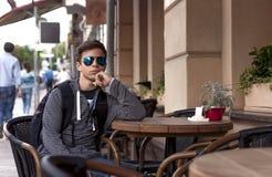 El sentarse de reclinación del hombre joven en una tabla en una calle de la ciudad Imagenes de archivo
