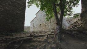 El sentarse de reclinación de la muchacha en raíces del árbol en territorio de la fortaleza defensiva antigua con la albañilería  metrajes