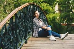 El sentarse de reclinación de la mujer joven en un puente de madera Foto de archivo libre de regalías
