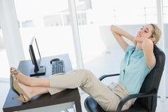 El sentarse de relajación de la empresaria joven con clase en su silla de eslabón giratorio Fotos de archivo