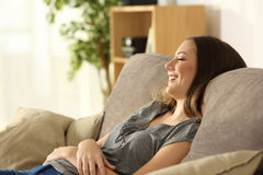 El sentarse de relajación de la muchacha en un sofá en casa Fotos de archivo