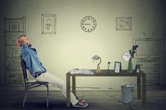 El sentarse de relajación del hombre de negocios en la oficina Fotografía de archivo libre de regalías