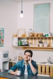 El sentarse de relajación del hombre joven en la cocina que habla en el teléfono imagen de archivo