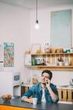 El sentarse de relajación del hombre joven en la cocina que habla en el teléfono imágenes de archivo libres de regalías