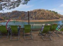 El sentarse de relajación de la gente en una silla por el lago Imagen de archivo