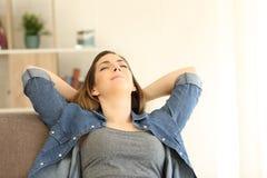 El sentarse de relajación de la mujer en un sofá en casa Foto de archivo libre de regalías
