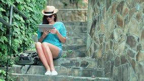 El sentarse de relajación de la mujer turística bonita del tiro lleno en las escaleras con los pasos de piedra usando la tableta almacen de video