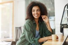 El sentarse de relajación de reclinación africano hermoso joven de la estudiante en café de consumición sonriente del café Fotografía de archivo