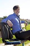 El sentarse de relajación sonriente del hombre de negocios en banch Imagenes de archivo