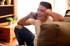 El sentarse de risa adolescente en el sofá que habla en el cierre del teléfono para arriba Fotos de archivo libres de regalías