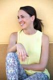 El sentarse de risa atractivo de la mujer joven Foto de archivo