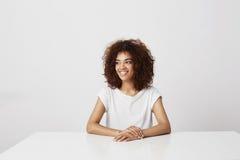 El sentarse de risa sonriente de la muchacha africana hermosa sobre el fondo blanco Copie el espacio Imagenes de archivo