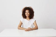 El sentarse de risa sonriente de la muchacha africana hermosa sobre el fondo blanco Copie el espacio Fotos de archivo libres de regalías