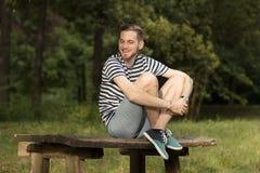 El sentarse de risa sonriente del hombre joven en la tabla de madera en delanteras de la naturaleza Foto de archivo