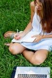 El sentarse de trabajo de la muchacha en la hierba Foto de archivo
