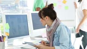 El sentarse de trabajo del diseñador creativo lindo en su escritorio