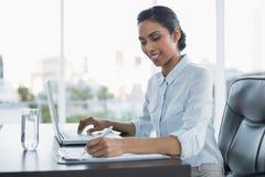 El sentarse de trabajo sonriente contento de la empresaria en su escritorio imagen de archivo