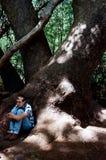 El sentarse debajo de un árbol grande Fotografía de archivo