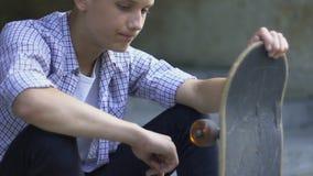 El sentarse del adolescente solo con el monopatín, agujereado sin los amigos, forastero almacen de metraje de vídeo