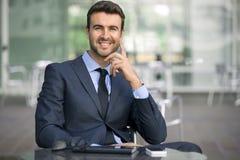 El sentarse del hombre de negocios confiado con el retrato de la sonrisa Imagenes de archivo