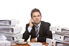 El sentarse del hombre de negocios seguro de sí mismo en el escritorio Fotografía de archivo libre de regalías
