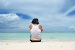 El sentarse del hombre solo en la playa Imagenes de archivo