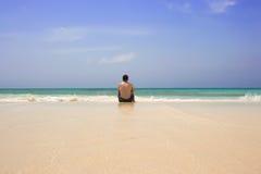 El sentarse del hombre solo en la playa Imágenes de archivo libres de regalías