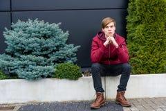 El sentarse del muchacho del adolescente al aire libre en la ciudad que piensa y que espera Foto de archivo
