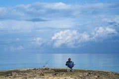 El sentarse del pescador relajado con un cielo azul Fotos de archivo libres de regalías