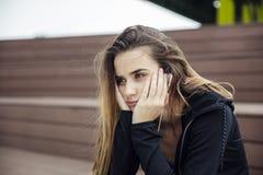 El sentarse deportivo triste y frustrado de la mujer joven al aire libre foto de archivo libre de regalías
