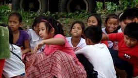 El sentarse elemental de los alumnos, cubriendo sus cabezas como les enseñan a comportarse durante la situación del terremoto del almacen de video
