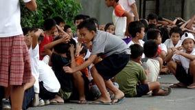 El sentarse elemental de los alumnos, cubriendo sus cabezas como les enseñan a comportarse durante la situación del terremoto del almacen de metraje de vídeo