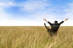 El sentarse emocionado del hombre de negocios al aire libre Imagenes de archivo