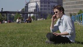 El sentarse en de la hierba y teléfono la llamada