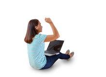 El sentarse en el piso con un ordenador portátil que aumenta sus brazos con una mirada Imagen de archivo