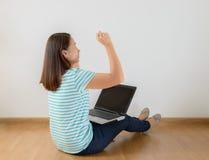 El sentarse en el piso con un ordenador portátil que aumenta sus brazos con una mirada Imágenes de archivo libres de regalías