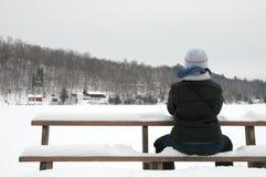 El sentarse en la nieve Imagenes de archivo