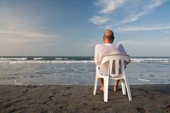 El sentarse en la playa imagenes de archivo