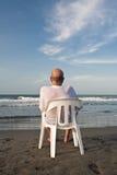 El sentarse en la playa fotos de archivo