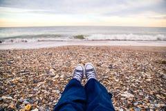 El sentarse en la playa Foto de archivo libre de regalías