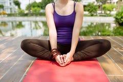 El sentarse en la posición de la yoga Imagen de archivo libre de regalías