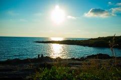El sentarse en las rocas con Sun que va abajo Imagen de archivo