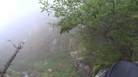 El sentarse en un acantilado Piernas que cuelgan sobre la cascada Cantidad épica El borde de la cascada metrajes