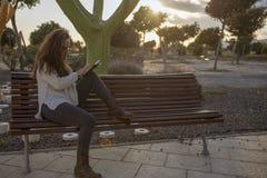 El sentarse en un parque en la lectura de la puesta del sol foto de archivo