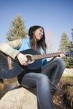 El sentarse en una roca que toca la guitarra Foto de archivo