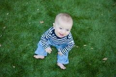 El sentarse feliz del bebé un césped verde Foto de archivo libre de regalías