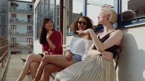 El sentarse femenino de los amigos al aire libre y cotilleo almacen de video