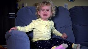 El sentarse gritador subrayado de la niña linda en el sofá almacen de metraje de vídeo