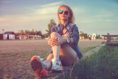 El sentarse hermoso de las gafas de sol de la mujer joven de la moda Fotos de archivo libres de regalías