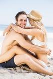 El sentarse joven de los pares cara a cara en la playa Imágenes de archivo libres de regalías